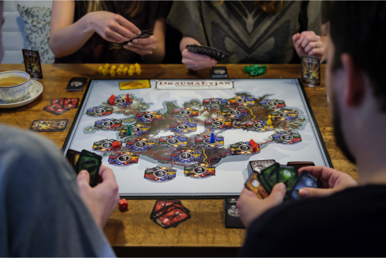 fyra vuxna som spelar Draumaeyjan brädspel som produceras av Cartamundi